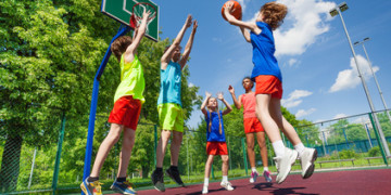 Teens jump for ball during basketball game on the ground at sunny summer day together